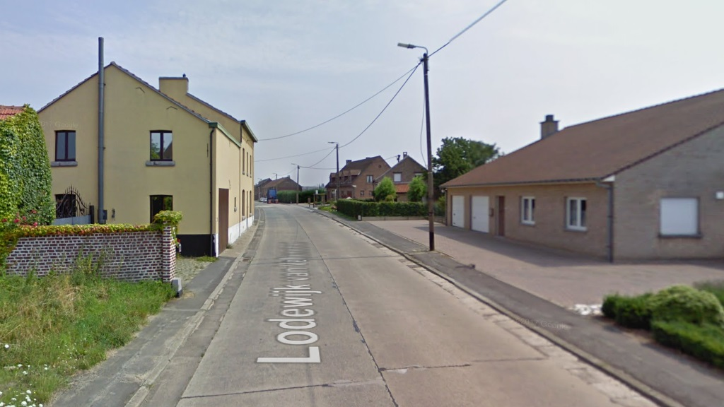 Lodewijk van Veltemstraat in Beisem in 2009, before the reconstruction. Continuous two lanes on the carriageway, but interrupted cycle path and extremely narrow pavement. Photo credit: Google Street View.