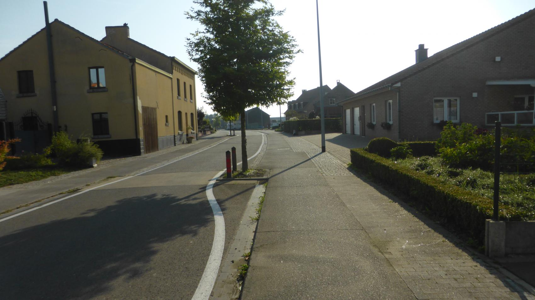 The same location in 2017. Carriageway narrowed, cycle paths continuous and wider, additional section of pavement for pedestrians. There is even space for trees!