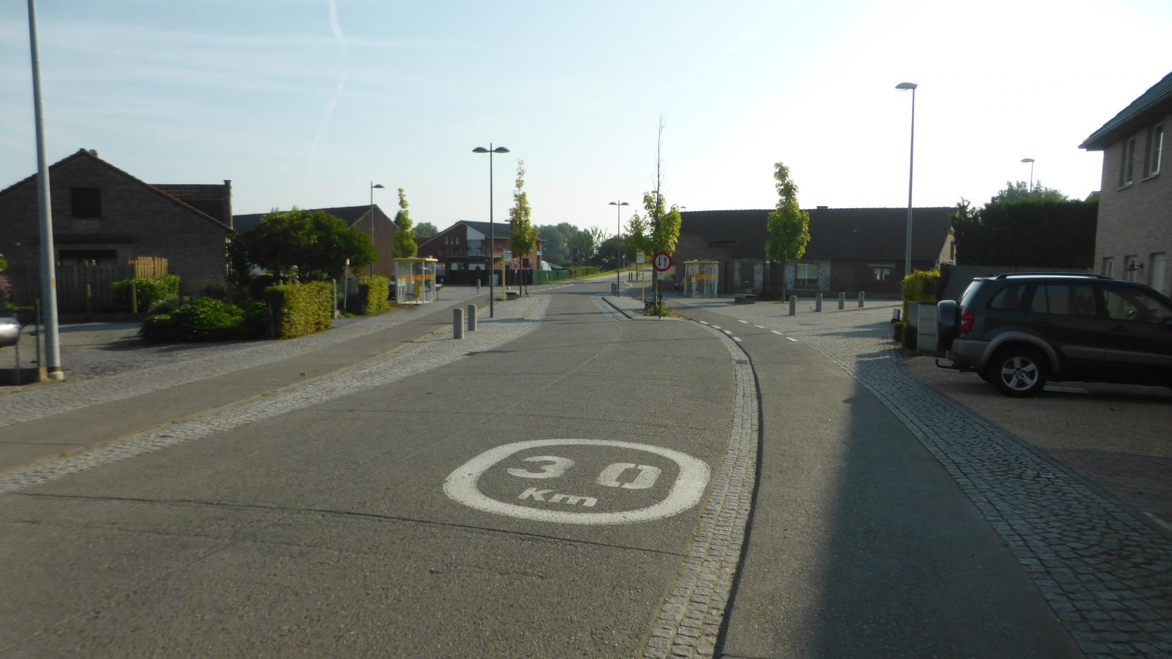Bus stop Kerkstraat on Lodewijk van Veltemstraat in Beisem. Carriageway narrowed to one lane to provide extra space for passengers entering or leaving the bus without interrupting the cycle traffic.