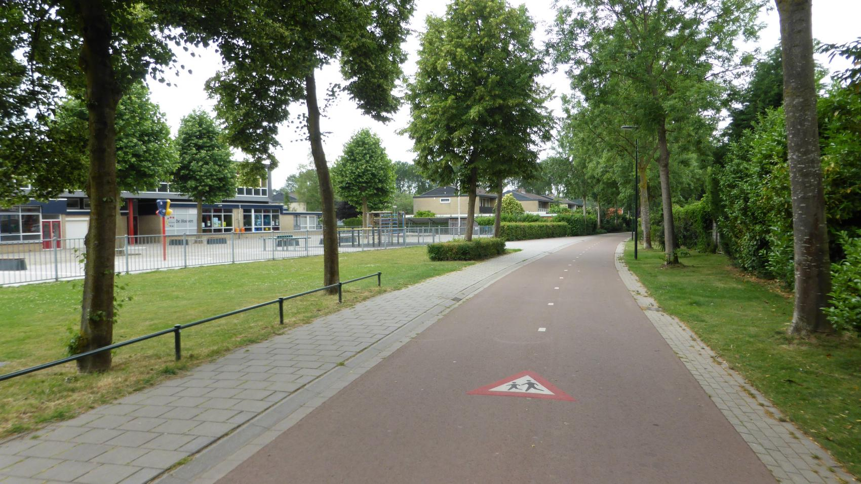 Until eighties this green corridor used to be a car road connecting Beuningen with Nijmegen. Now kids can travel to the catholic elementary school De Hoeven (left side of the picture) by bicycle without being endangered by car traffic.